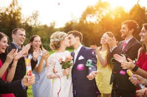 Ein frisch vermähltes Hochzeitspaar feiert mit Freunden.
