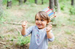 Kind spielt beim Fotoshooting mit Konfetti.