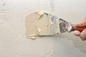 Spachtelarbeiten ebnen die Wand.