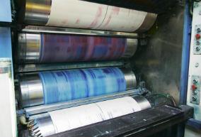 Eine Druckerei stellt Druckerzeugnisse wie Prospekte, Broschüren, Zeitungen oder Flyer im Ein- und Mehrfarbendruck her.